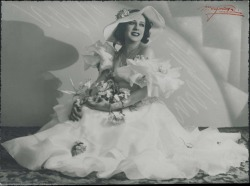 Fotografía de actriz sin identificar, sentada con vestido blanco, sombrero y ramo de flores.